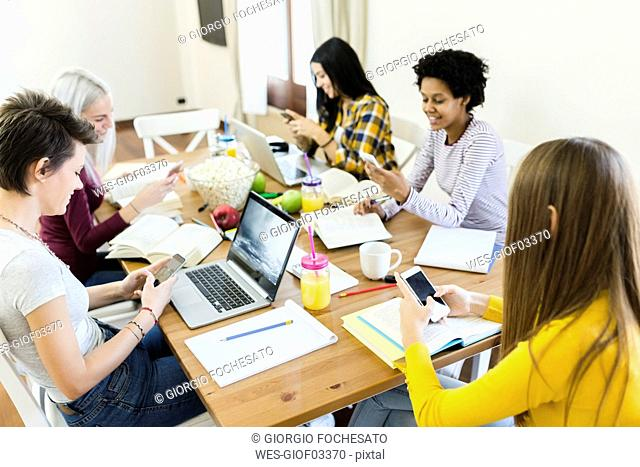 Group of female students using cell phone at table at home