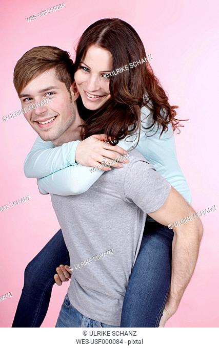 Young man giving piggy back ride to woman, smiling, portrait