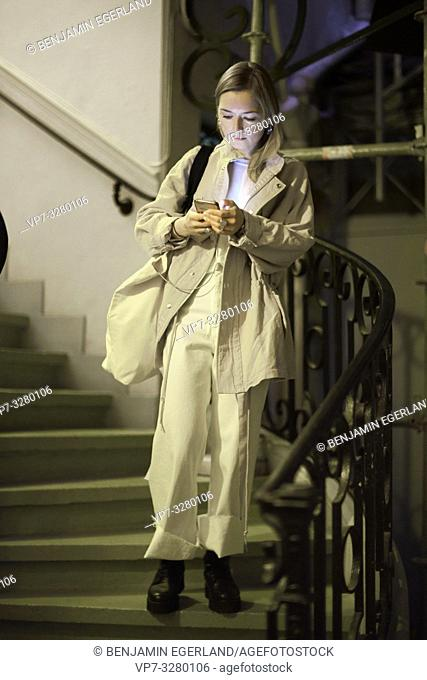 fashionable woman using smartphone while standing on stairs, during fashion week, in Paris, France