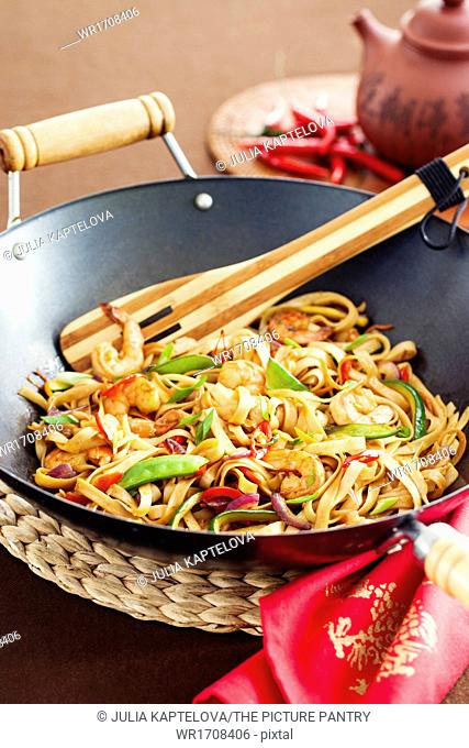 Asian stir fried noodle with vegetabled and prawns in wok