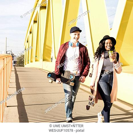Young couple with skateboard walking on bridge