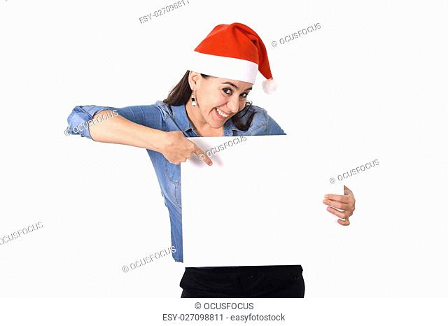 young attractive Hispanic woman wearing Santa Claus Christmas hat and blue shirt holding and p˜inting blank billboard or placard sign as copy space for adding...