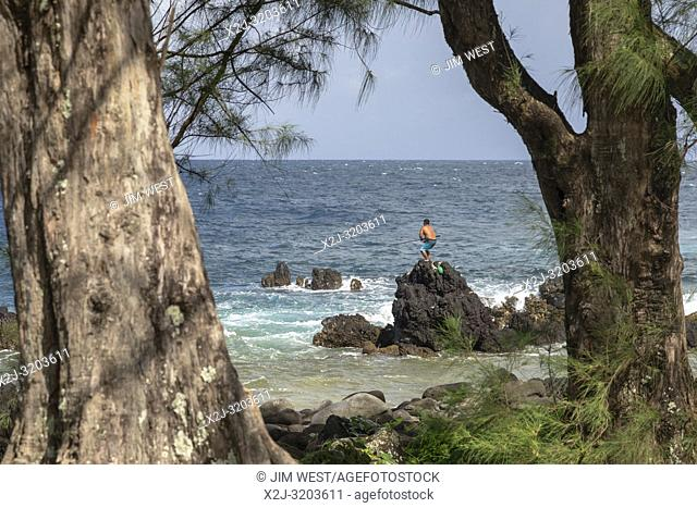 LaupÄ. hoehoe, Hawaii - LaupÄ. hoehoe Point. A man balances on rocks while fishing in the surf