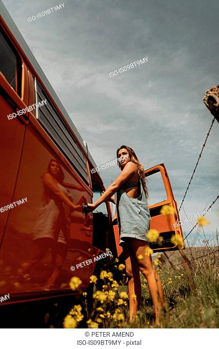 Young woman standing by recreational vehicle on rural roadside, Jalama, California, USA