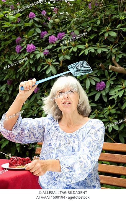 Elderly lady with piece of cake and flyswatter