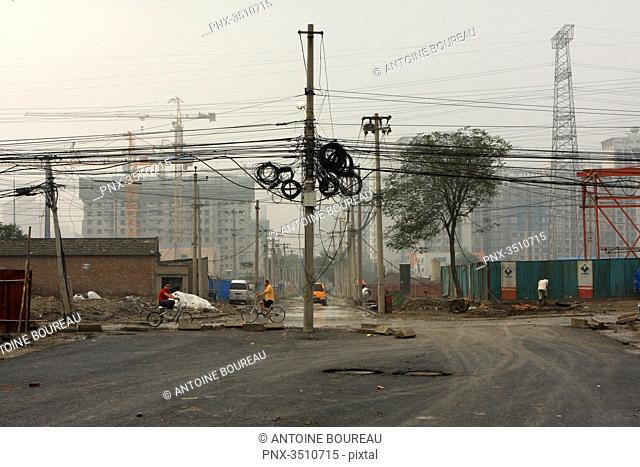 China, Beijing, Electric pylon covered with cable in an old hutong district being transformed into a residential area composed of building of around thirty...