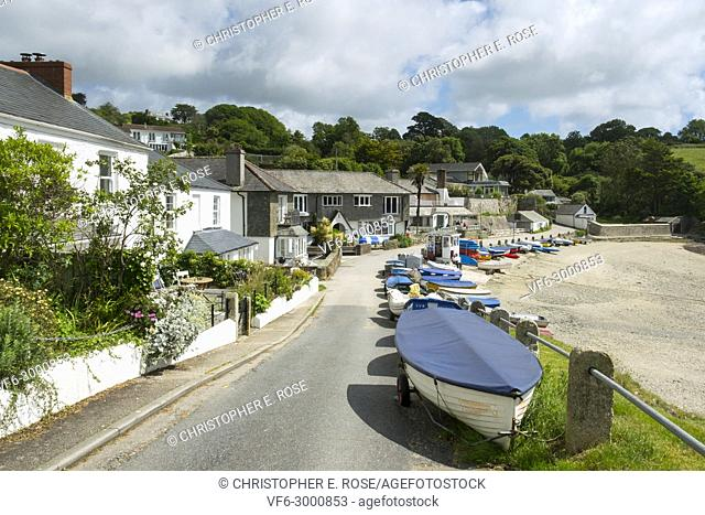 Many colourful small boats line up along the roadside beach edge in the popular launching place of Helford Passage, Cornwall, UK