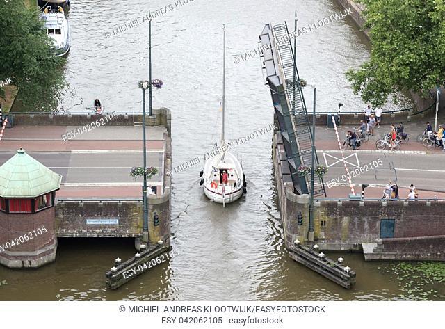 Leeuwarden, the Netherlands, 10 june 2018: Open bridge in the dutch waterways during the tourist season on june 10, 2018 in Leeuwarden, the Netherlands