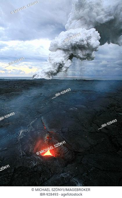 Clouds of smoke and a so-called Skylight, where you can see the still flowing molten lava under the solidified lava, Eastern Rift Zone, Kilauea Volcano