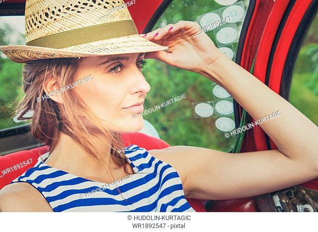Woman with sun hat on back seat of vintage car day dreaming