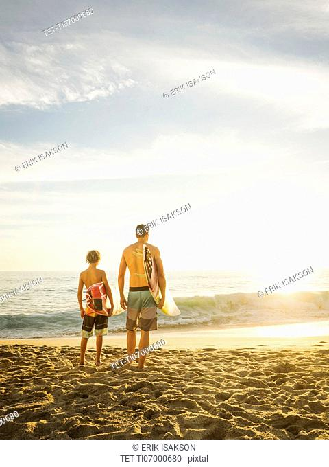 Father and son (14-15) looking at sea