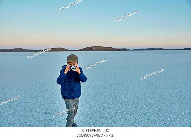 Young boy standing on salt flats, looking through camera, Salar de Uyuni, Uyuni, Oruro, Bolivia, South America