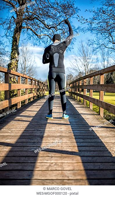 Spain, Gijon, athlete standing on wooden bridge