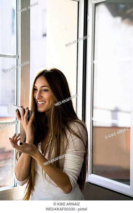 Smiling young woman using cell phone at the window