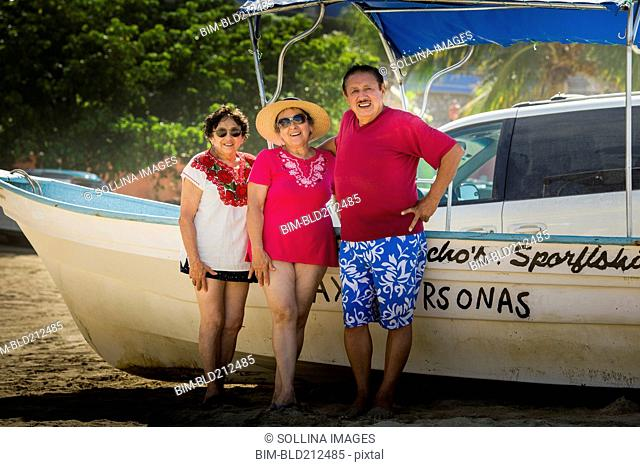Hispanic friends smiling by boat on beach