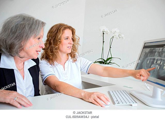 Mature woman showing senior woman x-ray image pointing at computer screen