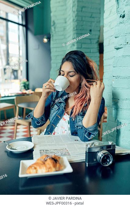 Woman sitting in coffee shop drinking coffee