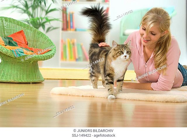 young woman fondling Maine Coon cat