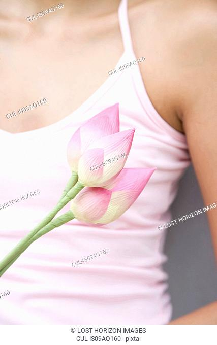 Cropped close up of woman with pink lotus flowers, Ari Atoll, Maldives
