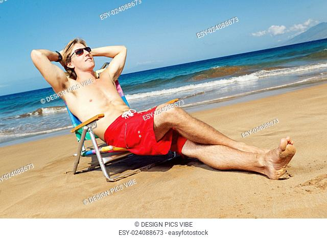 Portrait of calm young man relaxing on the beach