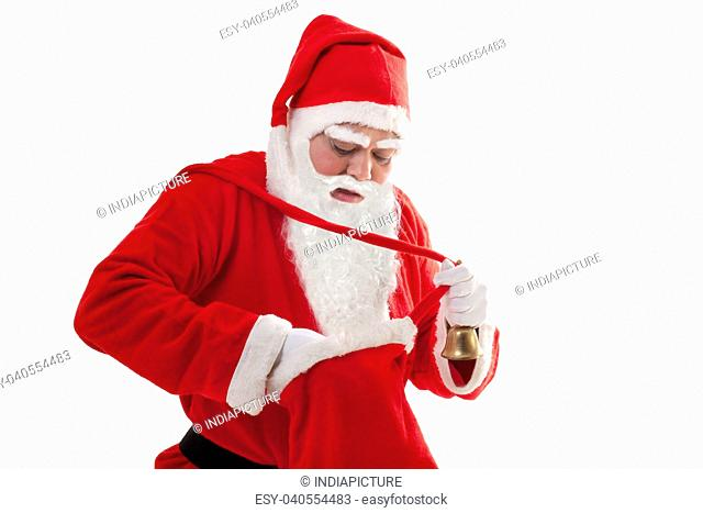 Santa Claus searching for something in bag white standing over white background