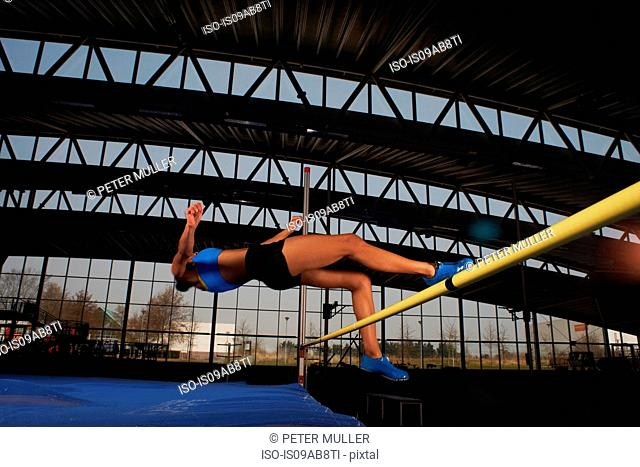 Young female athlete doing high jump