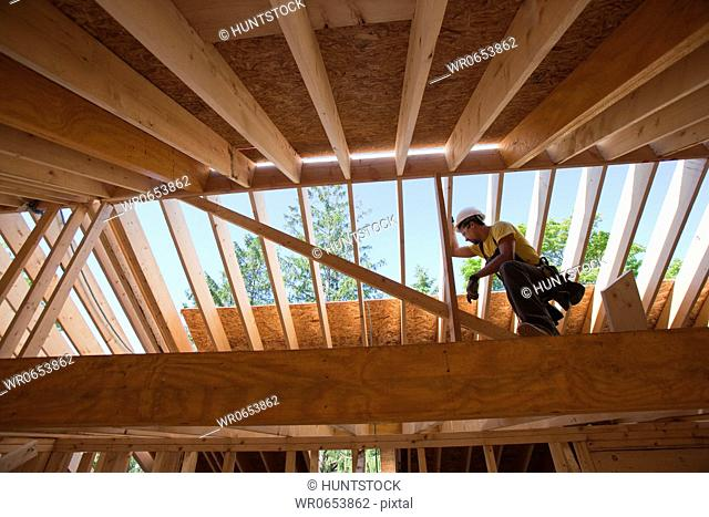 Hispanic carpenter using circular saw on rafter at a house under construction