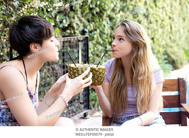 Two young women drinking cocktails in pineapples outside