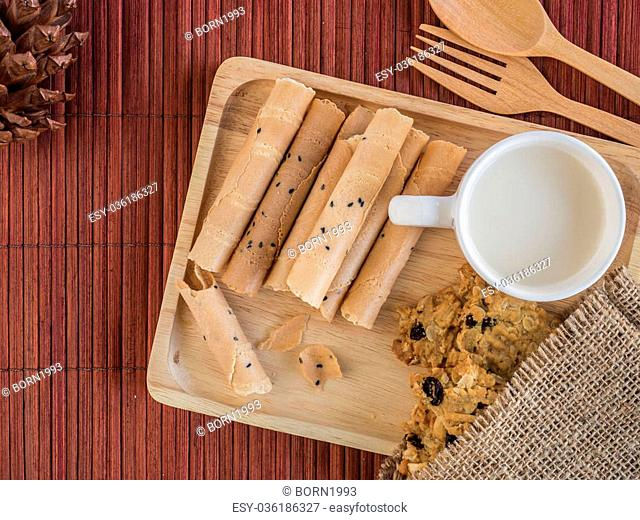 Thai rolled wafer and cookie with cup of milk in wooden tray on bamboo placemat in wooden tray on bamboo placemat