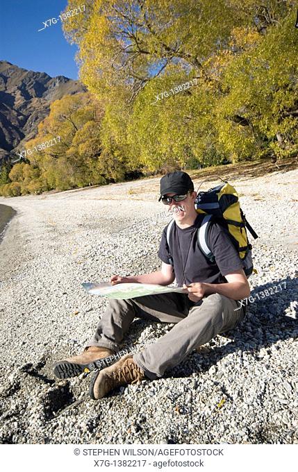 YYoung hiker reading a map at Glendhu Bay on the shores of Lake Wanaka, South Island of New Zealand