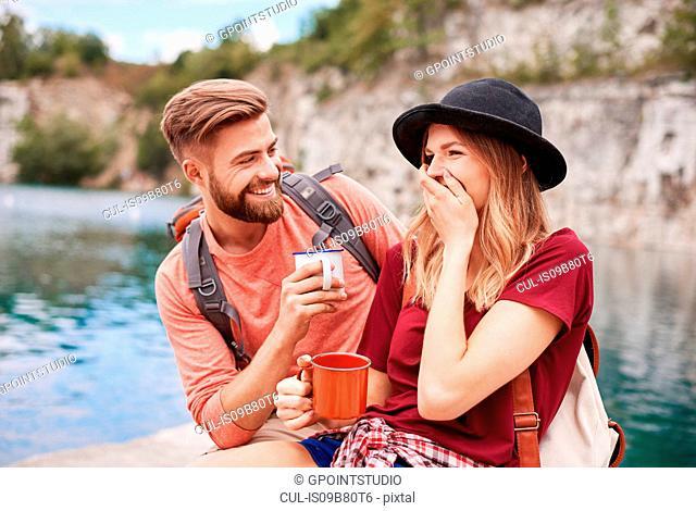 Couple by water holding enamel mugs smiling, Krakow, Malopolskie, Poland, Europe