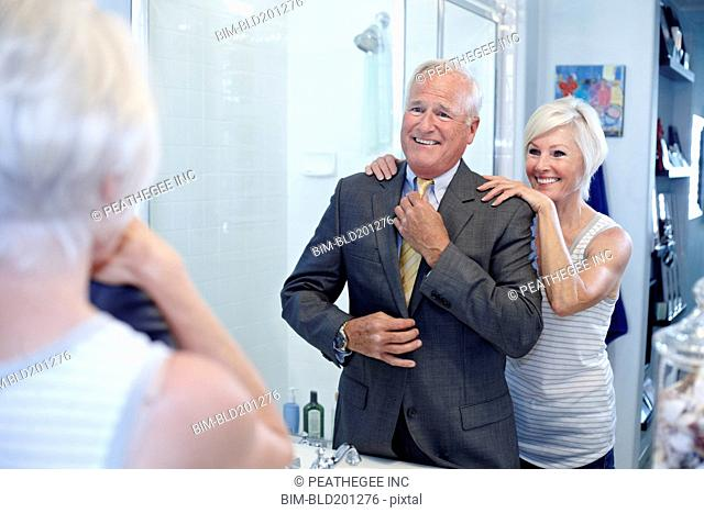 Caucasian couple dressing in bathroom