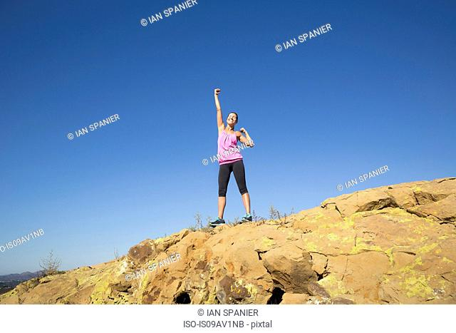 Female runner celebrating on top of hill, Thousand Oaks, California, USA