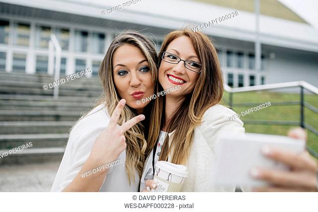 Two women taking selfie with smartphone outdoors