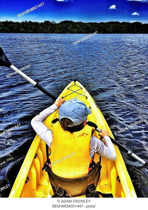 Boy kayaking in rural lake