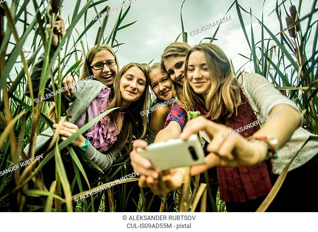 Five young women taking self portrait in marshes