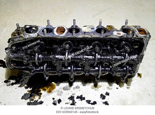 The head of the block of cylinders. The head of the block of cylinders removed from the engine for repair. Parts in engine oil