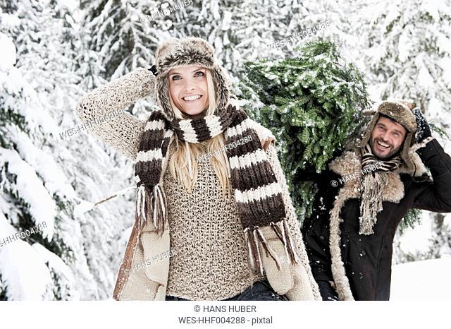 Austria, Salzburg County, Man and woman walking through snow while man carrying christmas tree