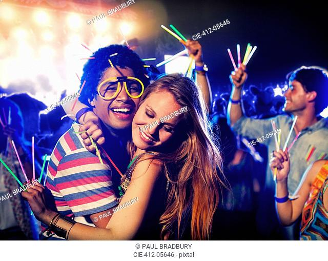 Couple with glow sticks hugging at music festival
