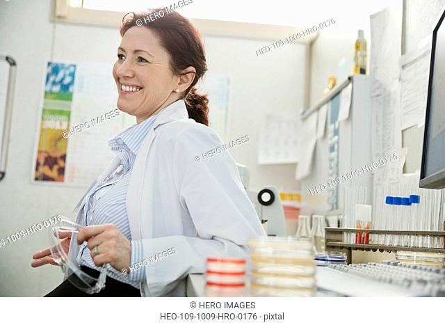 Happy female doctor looking away while leaning on desk in lab