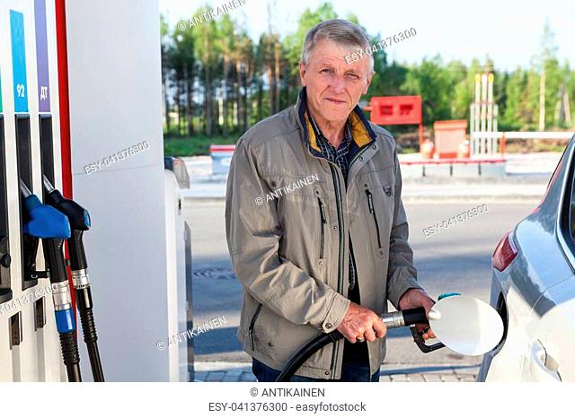 An elderly man is on gas station with a fuelling nozzle in hands