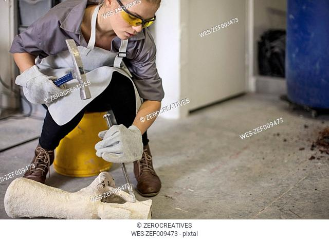 Woman breaking off casts with hammer and chisel