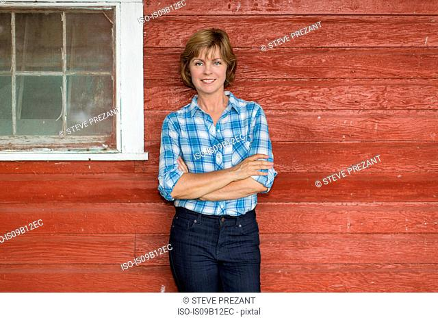 Portrait of mature woman with arms folded in porch