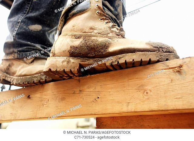 Construction worker muddy boots standing on wood plank from below