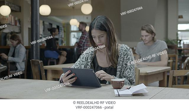 Woman using tablet and drinking coffee in pub