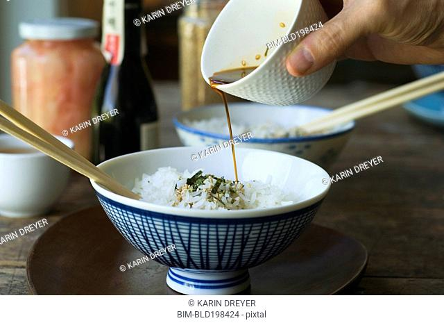 Person pouring sauce over bowl of rice