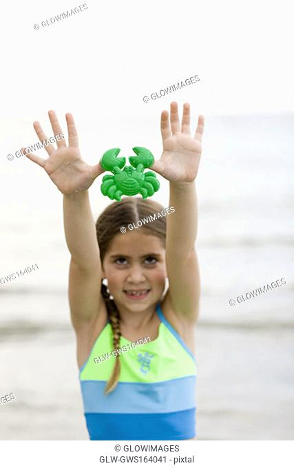 Close-up of a girl holding a toy on the beach