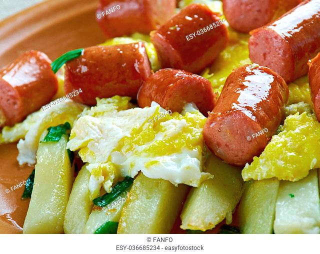 Huevos rotos con chistorra.scrambled eggs with sausage and potatoes. Mexican style