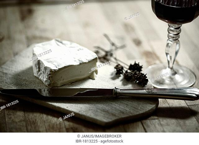 Soft cheese, red wine and knife on a table, still life