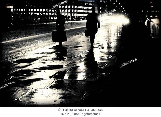 silhouette of two unrecognizable bussinesmen on a rainy night walking on the sidewalk, crossing London Bridge, City of London, England, UK